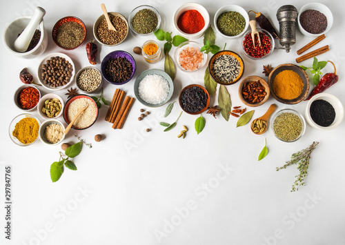 Obraz Various dry spices in small bowls and raw herbs flat lay on white background. Top view, copy space - fototapety do salonu