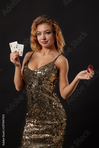 Fototapeta Ginger girl in shiny dress posing holding two playing cards and chips in her hands standing against black studio background. Casino, poker. Close-up. obraz na płótnie