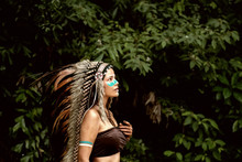 The Abstract Art Design Background Of Beautiful Woman Wearing Headdress Feathers Of Birds. American Indian Girl In Native Costume,posing In Forest,vintage And Art Tone,blurry Light Around
