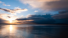 Stunningly Beautiful Sunrise, Taken On A Cloudy Morning From Salthill Beach Near Galway, Ireland. Showing The Calm Water Of Galway Bay And Mutton Island In The Distance.