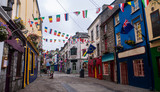 Fototapeta Uliczki - View of the main high street in Galway City with the brightly painted buildings and cobblestone streets on a cloudy day