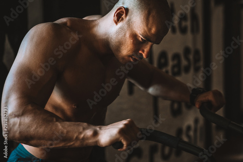 Fotografía  Muscular build athlete on exercise bike in a gym - Stock photo