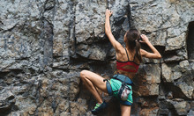 Young Slim Muscular Woman Rockclimber Climbing On Tough Sport Route, Climber Makes A Hard Move.