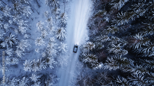 Fototapeta Aerial view of a car on winter road in the forest. Aerial photography of snowy forest with car on the road. Aerial photo.  obraz