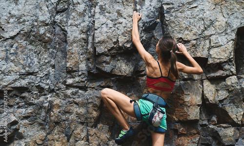 Fototapeta young slim muscular woman rockclimber climbing on tough sport route, climber makes a hard move