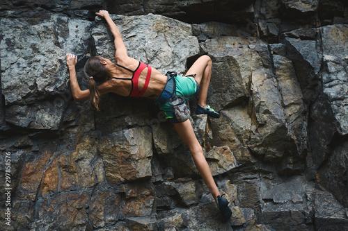 Fototapeta young slim muscular woman rockclimber climbing on tough sport route, climber makes a hard move. obraz
