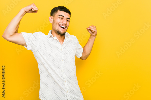 Fotomural  Young hispanic man raising fist after a victory, winner concept.