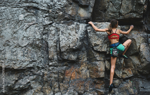 Obraz na plátně young slim muscular woman rockclimber climbing on tough sport route, climber makes a hard move