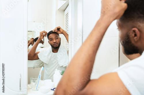 Foto  Young black man examining his hair, looking at bathroom mirror