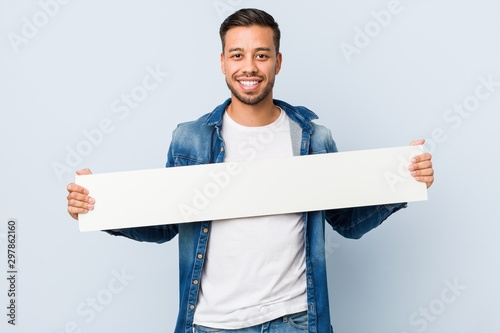 Obraz Young south-asian man holding a white placard. - fototapety do salonu