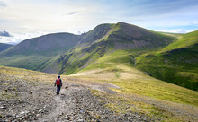 A Hiker And Their Dog Walking Along A Rugged Path On A Sunny Day Towards The Summits Of Crag Hill, Grasmoor And Sail In The Lake District, England, UK.