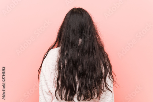 Young indian woman wearing pajama from behind, looking back.