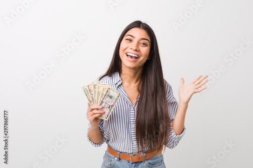 Young arab woman holding dollars celebrating a victory or success Wallpaper Mural