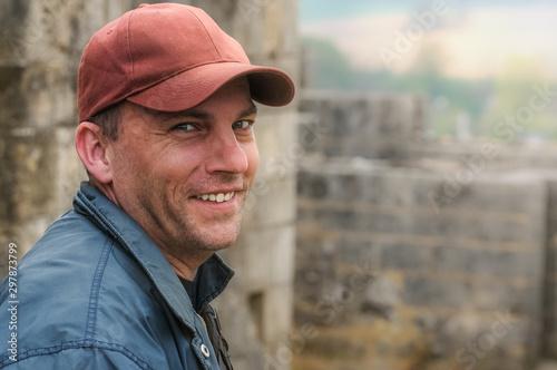 Portrait Mann in Freizeitkleidung auf alter Burg, im Gegenlicht aufgenommen #297873799