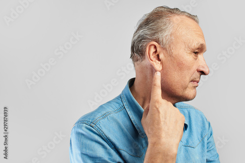 Fotomural  Portrait of middle aged caucasian man in profile pointig finger on his ear isolated on white with copy space