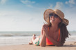 Beach woman funky happy and colorful wearing sunglasses and beach hat having summer fun during travel holidays vacation. Young trendy cool hipster woman in bikini lying in the sand.