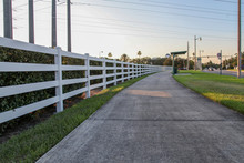 A Long, Curved White Wooden Fence Alongside A Grassy Walk In The Background Of The Beautiful Landscape Of Plants And Trees In The Late Afternoon In Celebration, Orlando, Florida, USA.