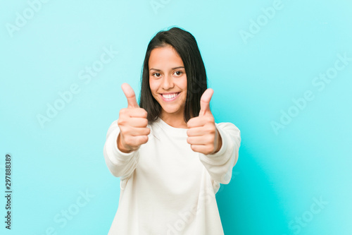 Young pretty hispanic woman with thumbs ups, cheers about something, support and respect concept Wallpaper Mural