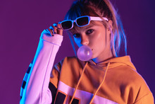 Stylish Pretty Young 20s Fashion Teen Girl Model Wear Glasses Blowing Bubble Gum Looking At Camera Standing At Purple Studio Background, Igen Teenager In Trendy Night Glow 80s 90s Concept, Portrait