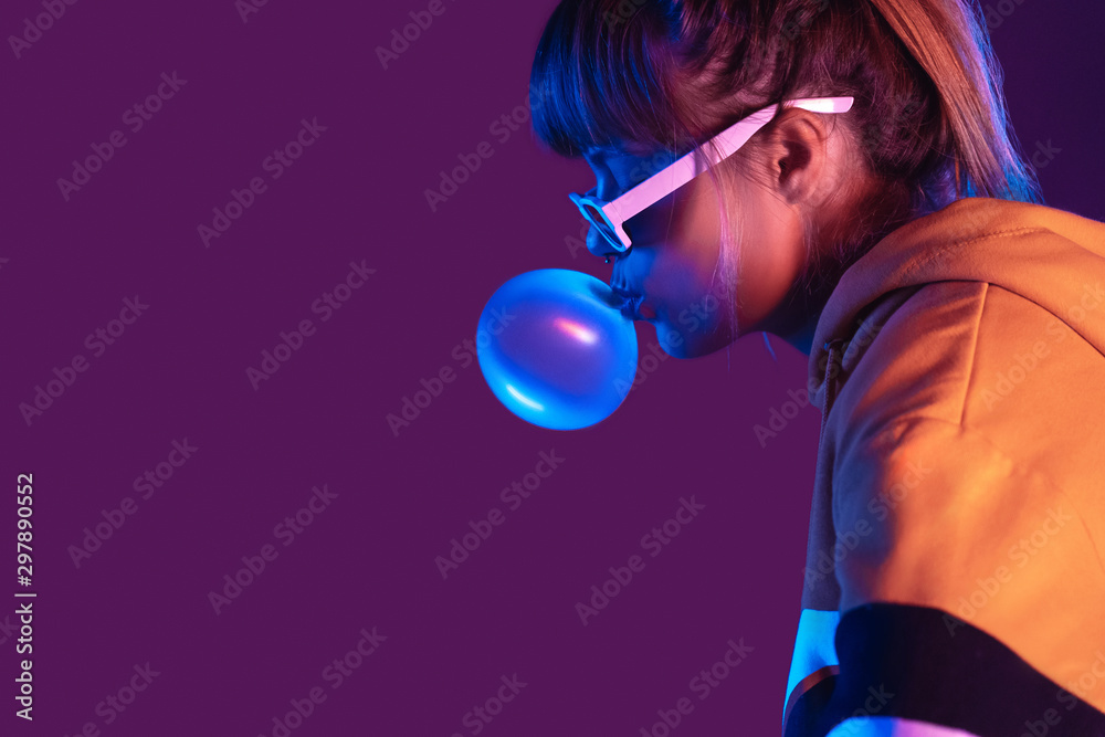 Fototapety, obrazy: Teen igen girl wear stylish trendy sunglasses and hoodie blowing bubble gum profile side view, pretty young woman fashion cool model with bubblegum 80s at party purple studio background, copy space