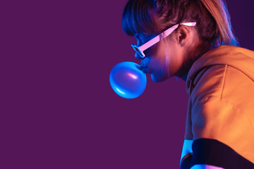 Teen igen girl wear stylish trendy sunglasses and hoodie blowing bubble gum p...