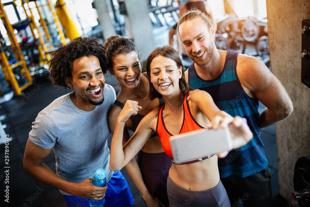 Fototapety, obrazy: Group of sportive people in a gym taking selfie. Concepts about lifestyle and sport in fitness club