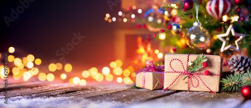 Fototapeta Christmas Home Room - Gift Box Below Tree With Lights And Fireplace obraz