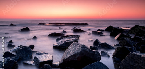 Keuken foto achterwand Lavendel stones in the smooth seawater in the red sunset time