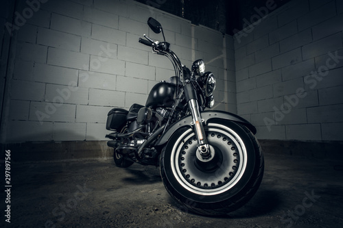 Amazing brand new motorbike is standing on the dark underground parking.