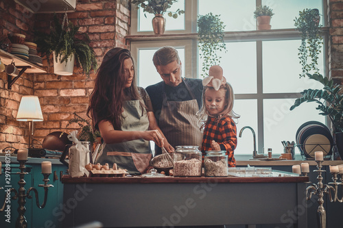 Fotografie, Obraz  Small happy family are cooking together something tasty for Halloween party