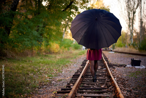 Fotomural  A girl with a black umbrella is walking on the railway.