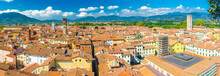 Aerial Top Panoramic View Of Historical Centre Medieval Town Lucca With Old Buildings, Typical Orange Terracotta Tiled Roofs And Mountain Range, Hills, Blue Sky White Clouds Background, Tuscany, Italy