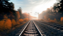 The Railway Turns To The Right. Blurred Background, Creating The Effect Of Movement. Beautiful Autumn Forest On The Sides Of The Railway