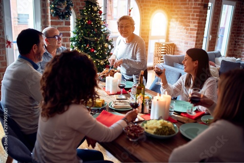 Fotomural  Family and friends dining at home celebrating christmas eve with traditional foo