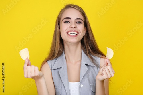 Pinturas sobre lienzo  Young beautiful girl with potato chips on yellow background