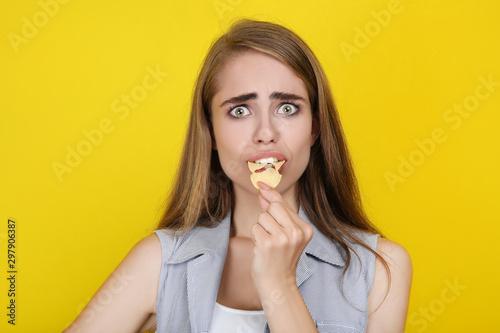 Pinturas sobre lienzo  Young beautiful girl eating potato chip on yellow background