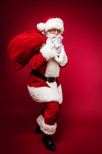 Children Are Waiting! A Full-length Photo Of Santa Claus, Posing On A Red Background Holding A Sack Full Of Presents On His Right Shoulder And Showing A Shush Sign With His Left Hand.