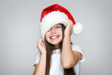 Little Girl In Christmas Hat On Grey Background