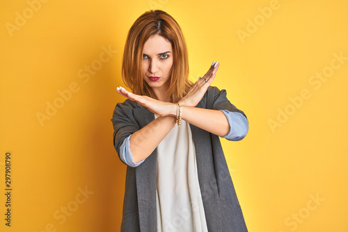 Fotografía  Redhead caucasian business woman over yellow isolated background Pointing with f