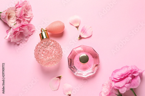 Flat lay composition with perfume bottles and flowers on light pink background - 297909772