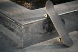 View of black skateboard in concrete skatepark on warm day