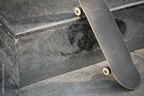 Fotografía View of black skateboard in concrete skatepark on warm day