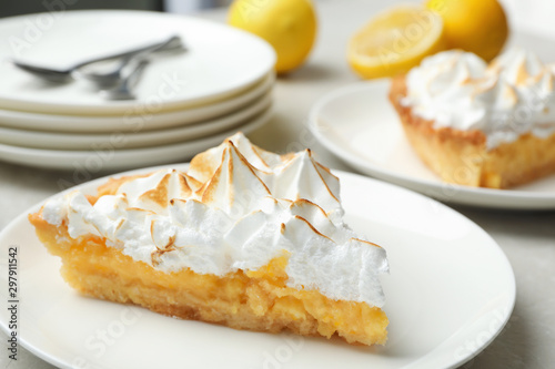 Valokuva  Plate with piece of delicious lemon meringue pie on light table