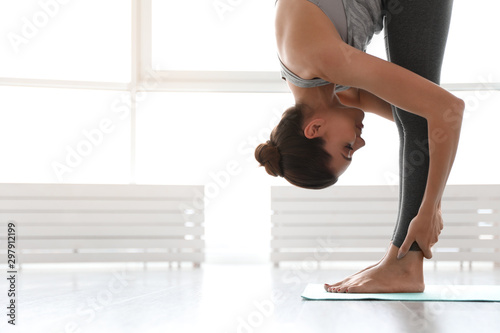 Photo Young woman practicing standing forward bend asana in yoga studio
