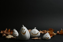 Jack-o-Lantern Candle Holders And Fallen Leaves On Black Background. Halloween Decor