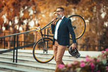 A Handsome Casual Middle-aged Businessman Is Going To The Office By Bicycle. He Is Carrying A Bicycle On His Shoulder Over The Stairs.