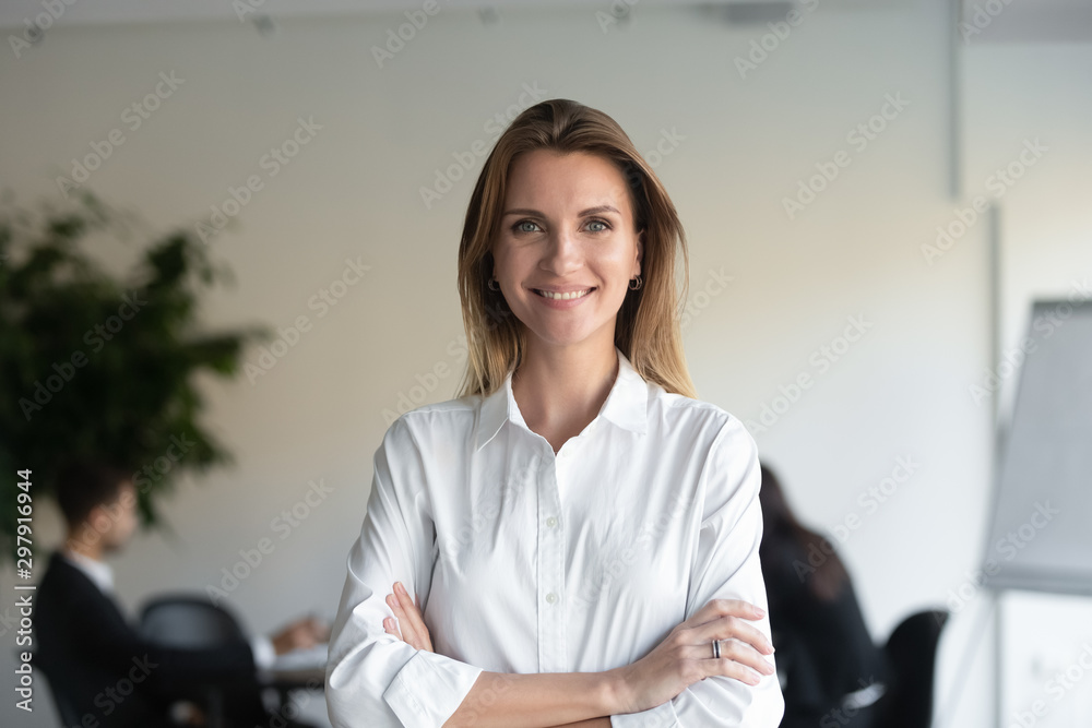 Fototapeta Smiling female professional manager standing arms crossed looking at camera