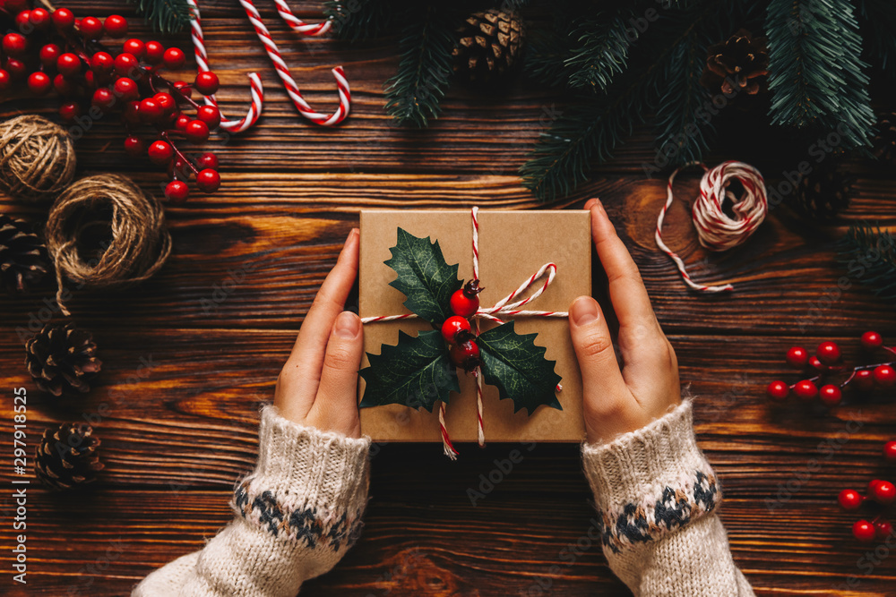 Fototapeta Christmas gift. Congratulations.Top wiew of woman holding traditional decorated gift box. Wooden table with cane,fir branches,fir cone, and berries