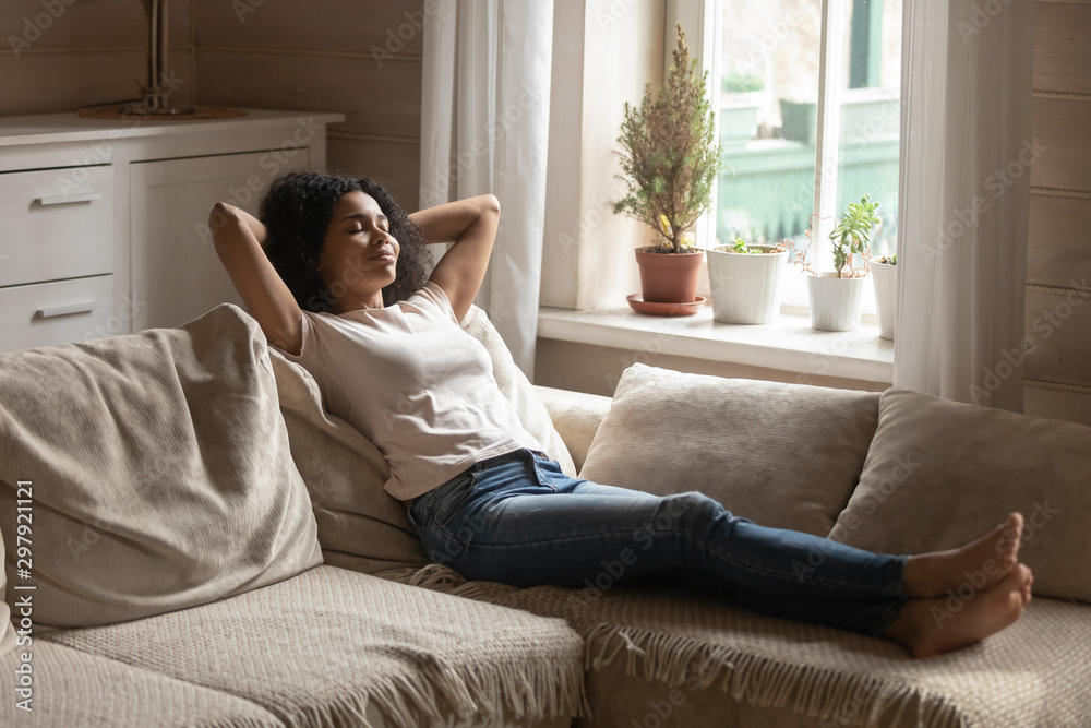 Fototapety, obrazy: Carefree happy african ethnicity young woman lying on comfortable sofa.