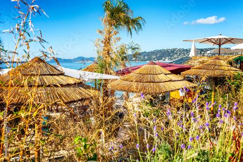 Montage in der Fensternische Honig Thatched umbrellas on the beach. Space for text.